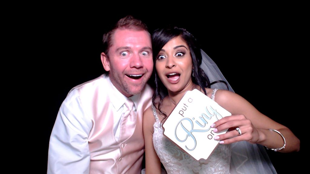 Bride and groom using the photo booth and photo booth props