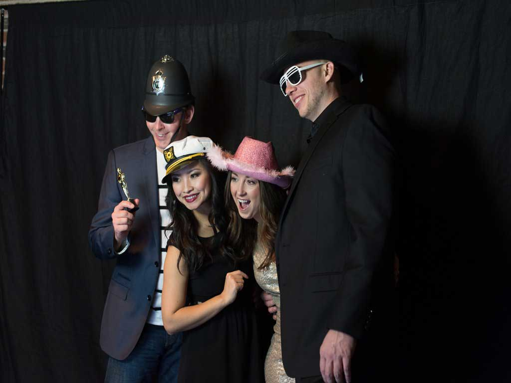 A group of couples having fun with props inside the Fashion Runway Photo Booth.