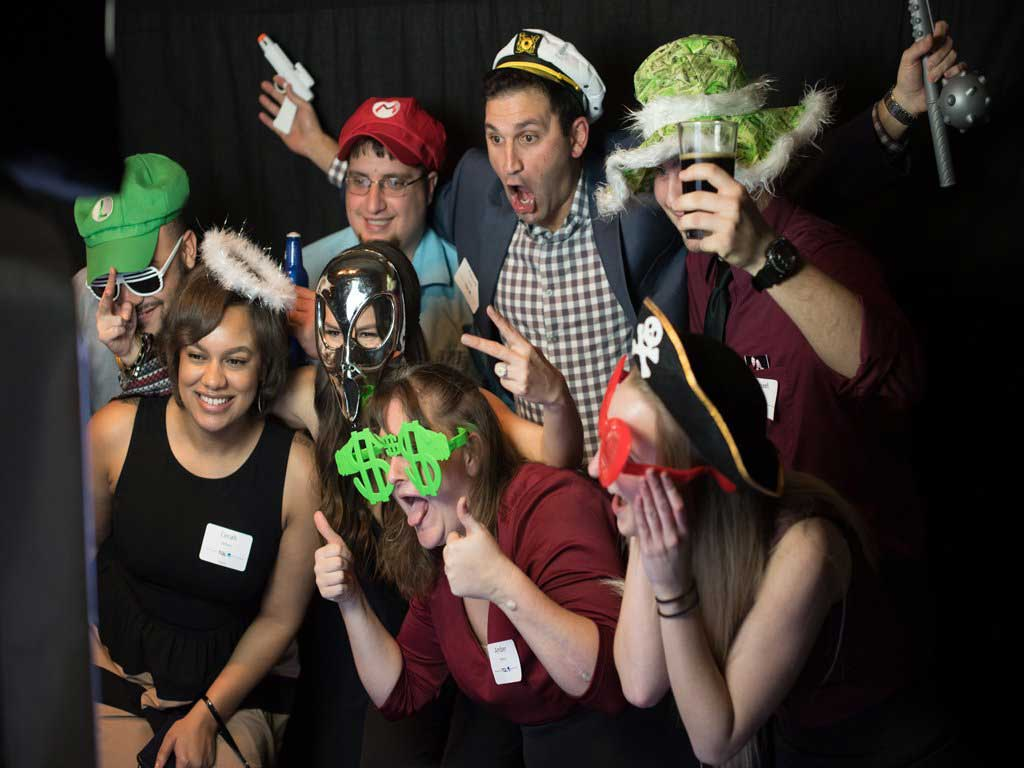 People having fun in front of the prop table with hats and masks on in front of our Big Black Photo Booth. Picture Perfect offers a large selection of over 100 props to have fun with.